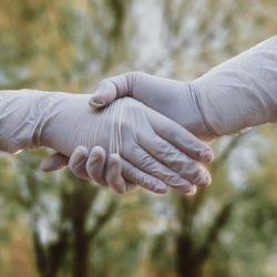 dwie ręcę w uścisku w gumowych rękawicach