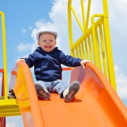 Roześmiane dziecko na kolorowej zjeżdzalni