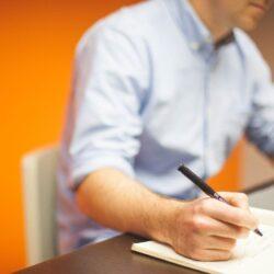 mężczyzna pisze w notesie
