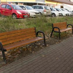 zdjecie dwóch ławek zamontowanych na pasie zielenie między ciągiem pieszym a parkingiem przy biedronce
