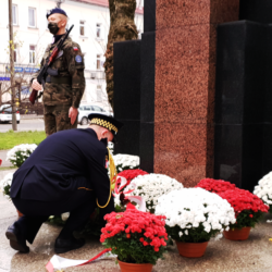 Straż Miejska składa biało-czerwone kwiaty przy pomniku i biało-czerwonych chryzantemach