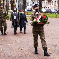 Uczeń w mundurze składa biało-czerwone kwiaty