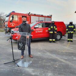 radny przemawia przy samochodzie strażackim