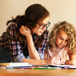 Zdjęcie przedstawia dorosłą obietę z brązowymi, długimi włosami nachyloną nad dzieckiem, dziewczynką. Obie patrzą na zeszyt. Zdjęcie obrazuje kobietę w domyśle mamę, która pomaga córce odrabiać lekcje.