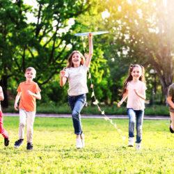 zdjęcie przedstawia radosne uśmiechnięte dzieci puszczające latawiec
